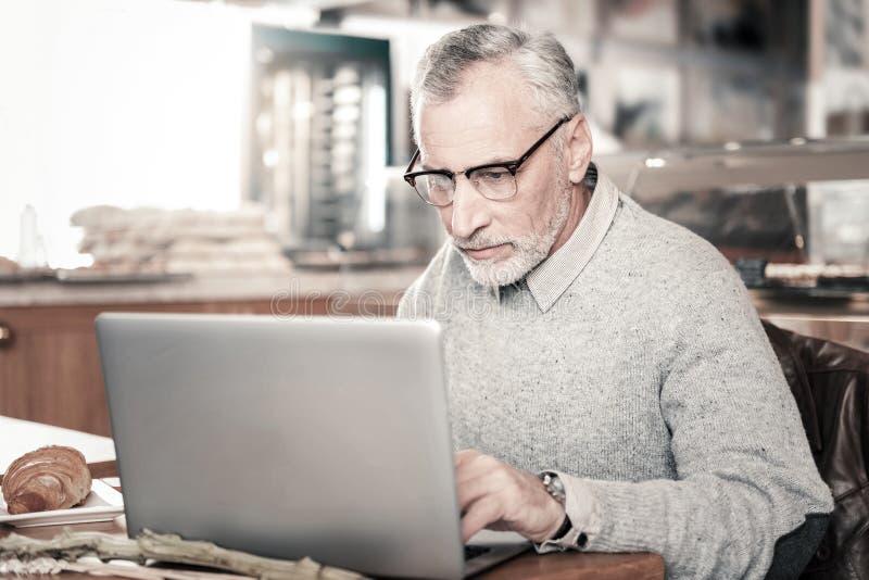 Aandachtige rijpe mens die zijn e-mail in Internet controleren stock afbeelding