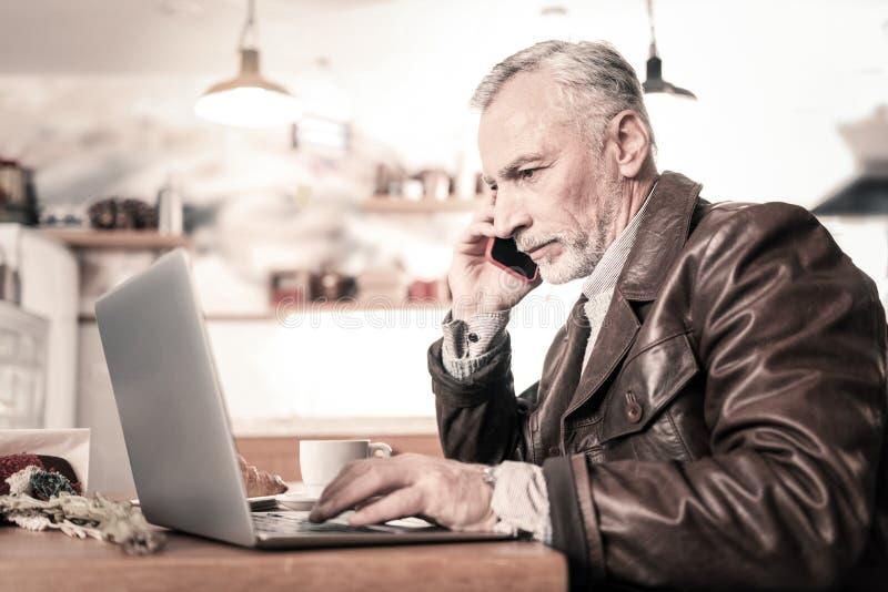 Aandachtige zakenman die per telefoon in koffie spreken stock foto