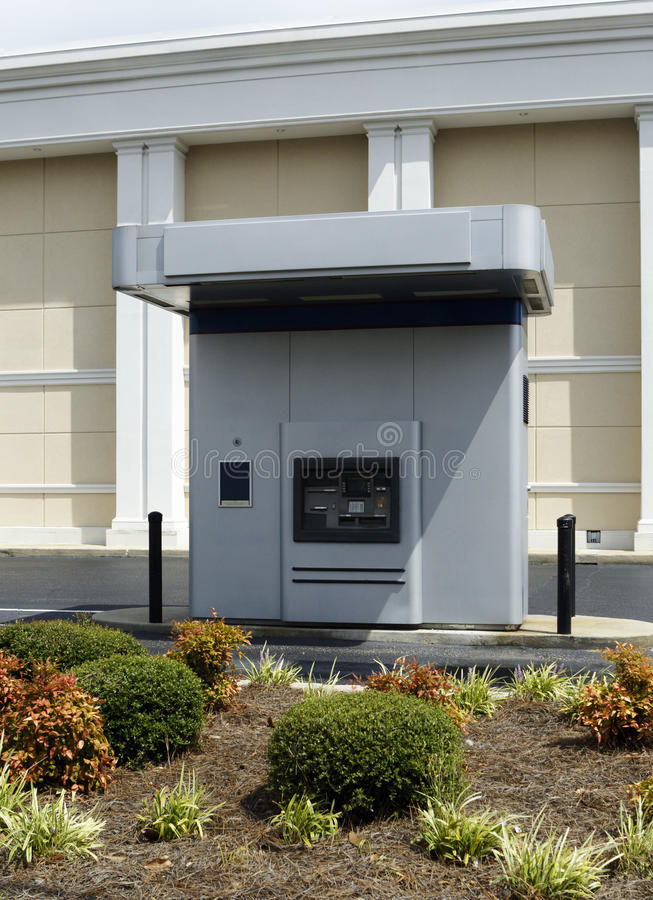 Aandrijving-op ATM-Machine naast een Bank stock afbeeldingen