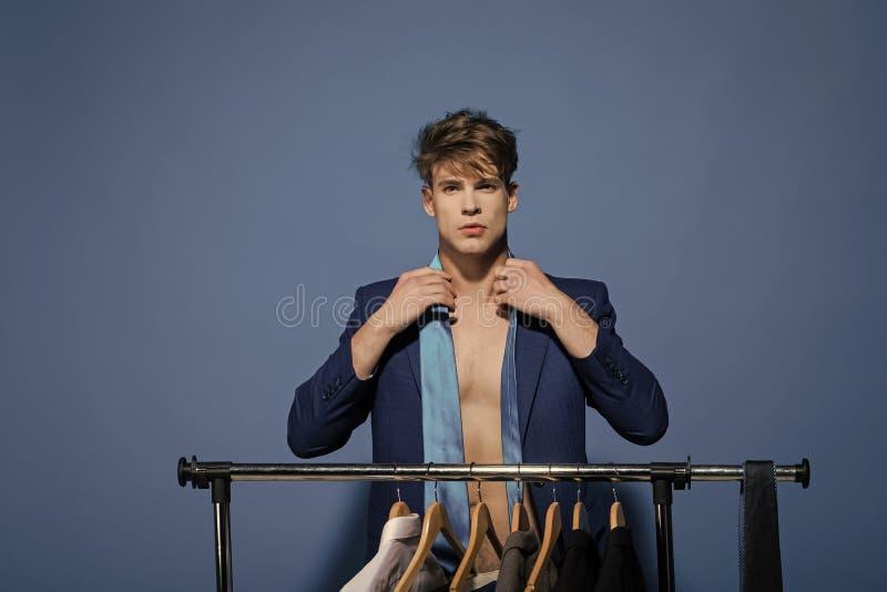 Aangedreven jongen De jongens van het kwestiesgezicht Zakenman geschikte band in jasje op naakt torso in garderobe royalty-vrije stock fotografie