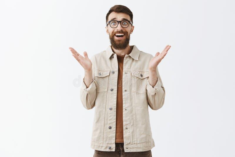 Aangenaam verraste knappe modieuze volwassen hipsterkerel met lange baard en modieus kapsel die palmen vreugdevol opheffen stock foto