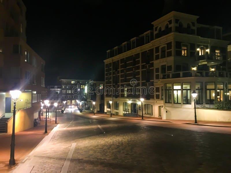 Aangestoken lantaarnpalen in de stadsstraten van Scheveningen Nederland met een groot flatgebouwgebouw op de achtergrond royalty-vrije stock afbeelding
