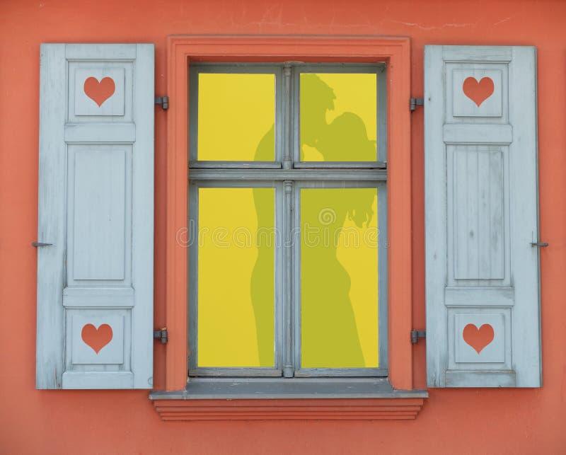 Aangestoken raamkozijn met een silhouet van een paar die liefde op een romantische dag maken, het conceptenachtergrond van de val stock foto's