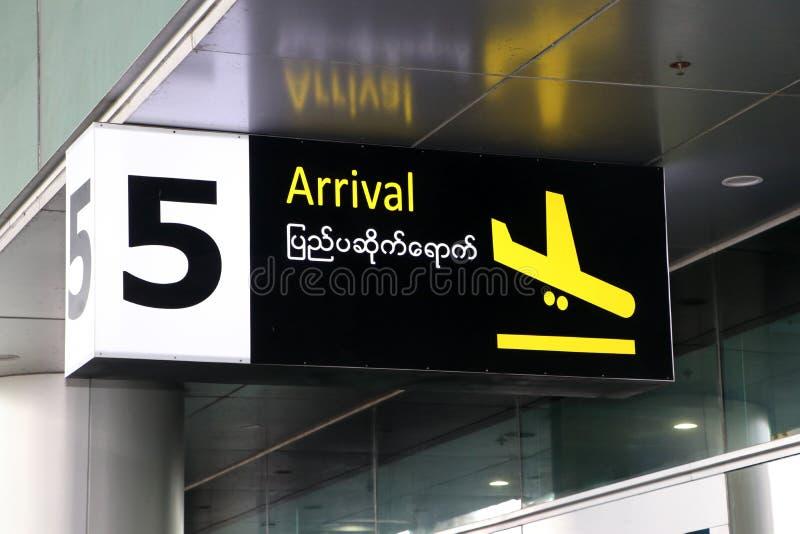 Aankomstteken in Engelse en Myanmar taal met symbool van het vliegtuig die in geel op zwarte kleur bij de poort nummer 5 landen royalty-vrije stock foto's