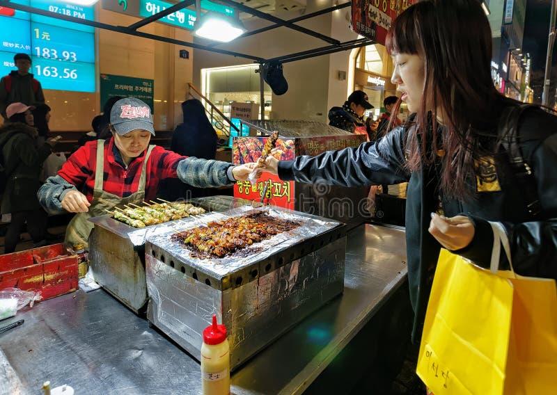 Aankoop van Kebabvleespennen in open de straatmarkt Seoel van Myeongdong royalty-vrije stock fotografie