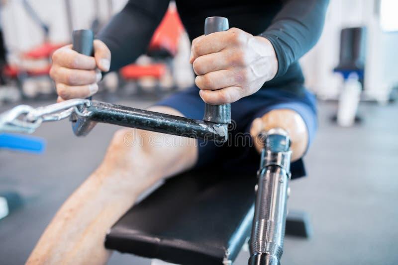Aanpassings Dichte omhooggaand van Atletenusing rowing machine royalty-vrije stock afbeeldingen