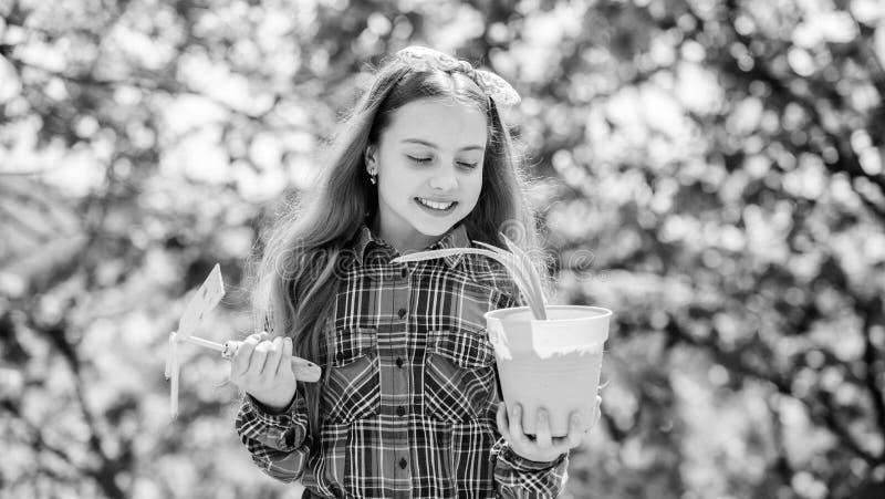 Aanplantseizoen Kindkind houdt bloempot en hoefijzer vast Gardening is vreedzame meditatieve bezetting royalty-vrije stock foto