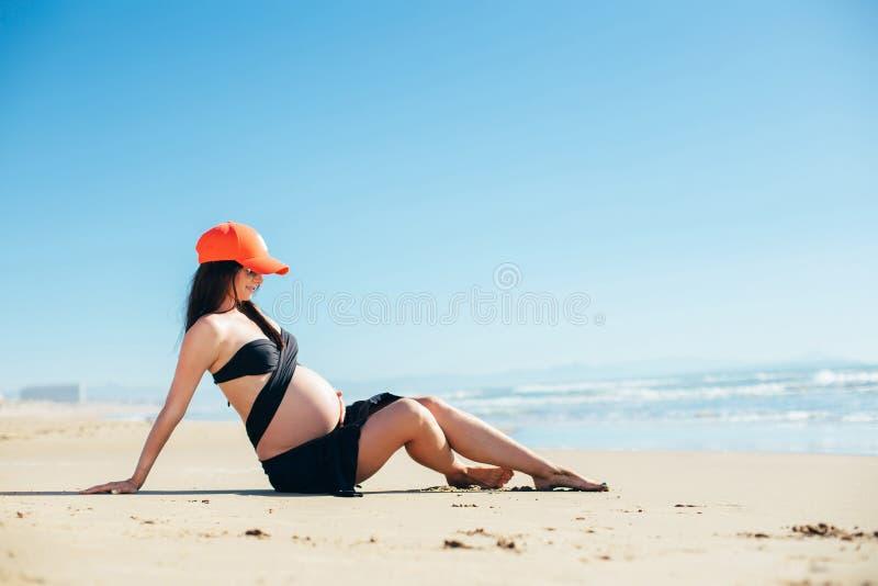Aanstaande moeder die op het zand liggen stock fotografie