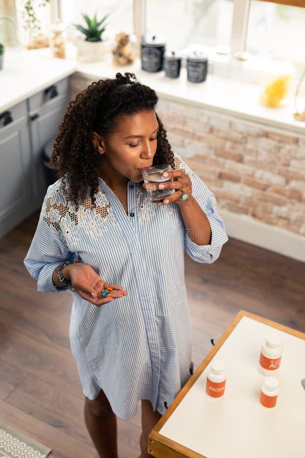 Aanstaande moederwas onderaan haar vitaminen met water royalty-vrije stock fotografie