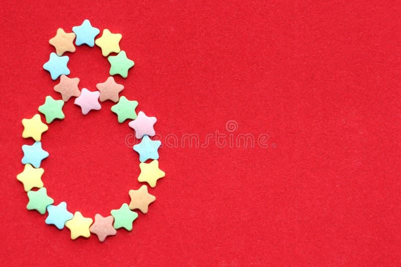 Aantal acht op een heldere rode achtergrond Acht gevoerd met kleine kleurrijke sterren stock foto's