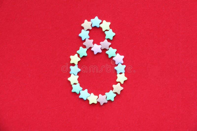 Aantal acht op een heldere rode achtergrond Acht gevoerd met kleine kleurrijke sterren royalty-vrije stock fotografie