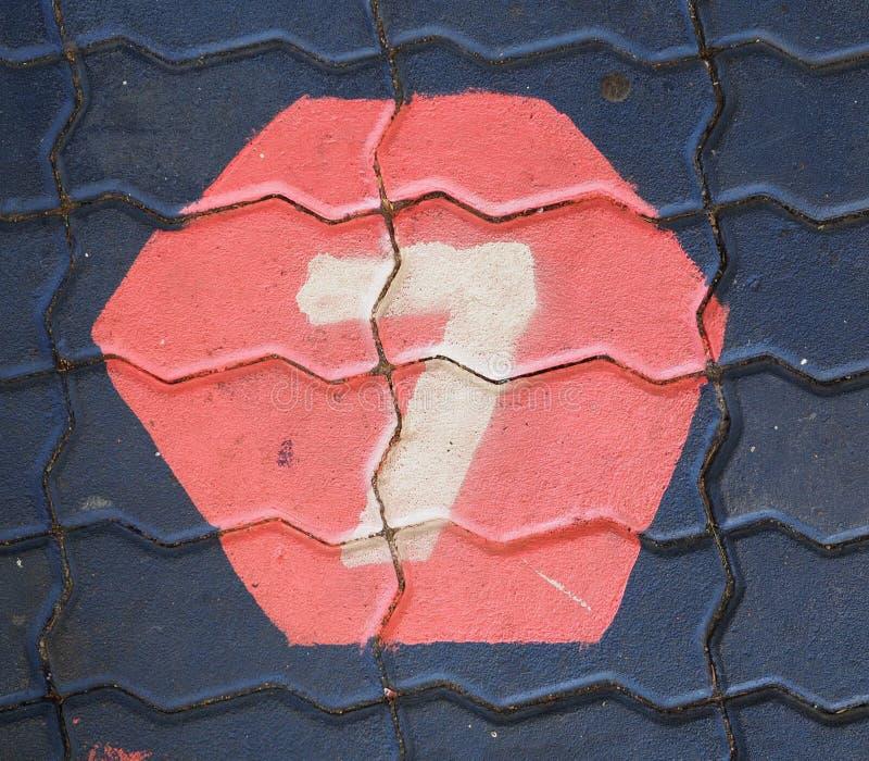 Aantal zeven in een zeshoek is op de voetpadspeelplaats royalty-vrije stock foto