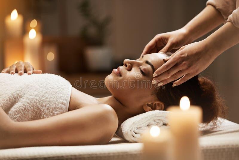 Aantrekkelijk Afrikaans meisje die gezichts van massage in kuuroordsalon genieten royalty-vrije stock afbeelding