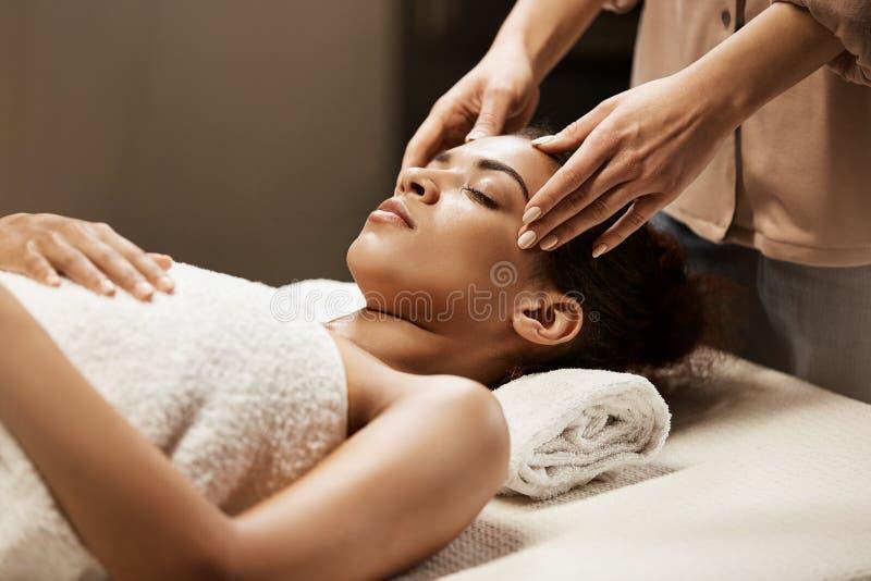 Aantrekkelijk Afrikaans meisje die gezichts van massage in kuuroordsalon genieten stock foto