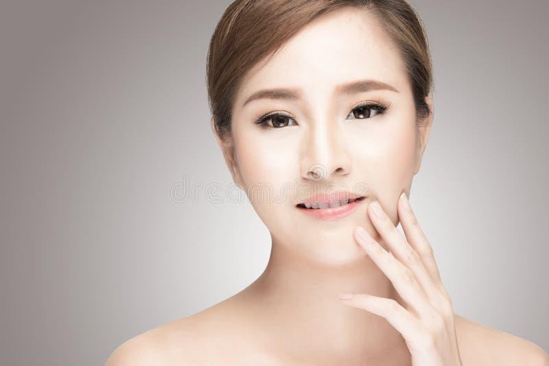 Aantrekkelijk Aziatisch de zorgbeeld van de vrouwenhuid op grijze achtergrond royalty-vrije stock foto's