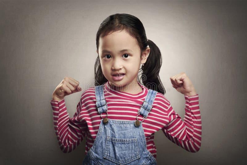 Aantrekkelijk Aziatisch meisje die haar spier tonen stock afbeelding