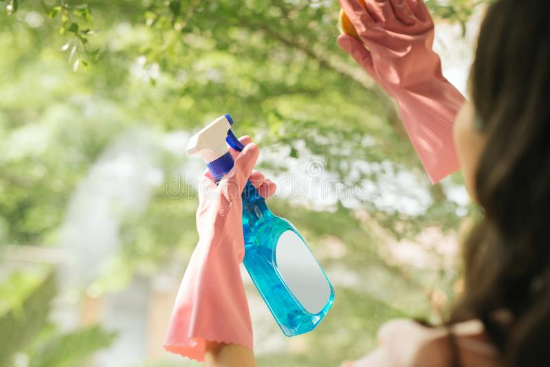 Aantrekkelijk Aziatisch meisjes schoonmakend glazen venster stock afbeeldingen