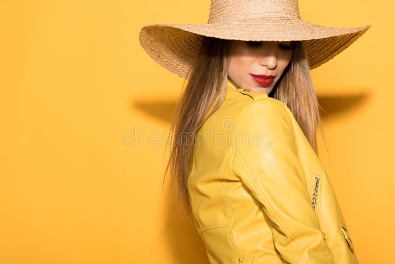 aantrekkelijk Aziatisch vrouwelijk model in strohoed het stellen op geel stock foto's