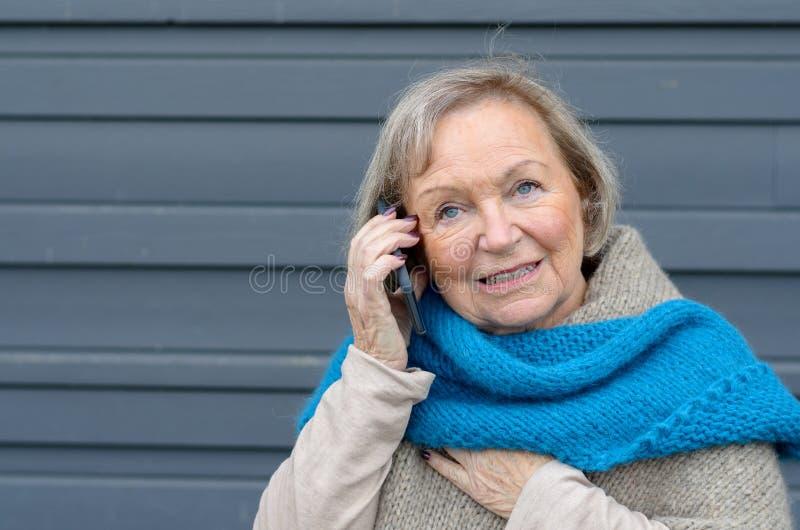 Aantrekkelijk bejaarde die op mobiel haar spreken royalty-vrije stock afbeelding