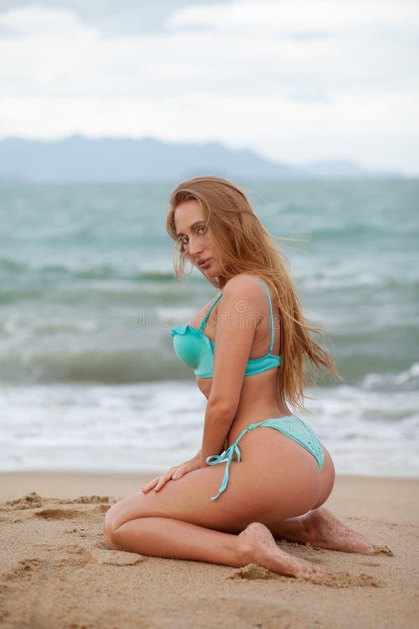 Aantrekkelijk bikinimodel met lange blonde haarzitting op het overzeese strand vietnam stock afbeelding