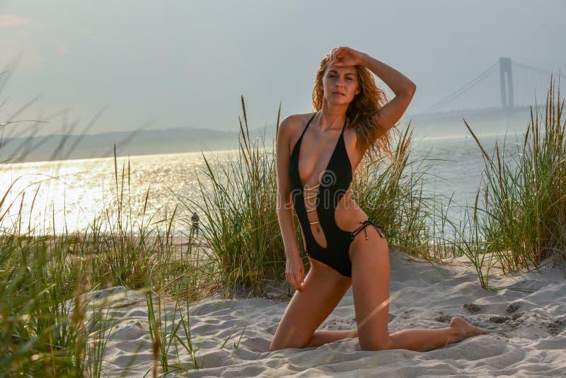 Aantrekkelijk blond meisje met perfect slank lichaam in het zwarte sexy zwempak stellen op het strand royalty-vrije stock foto's