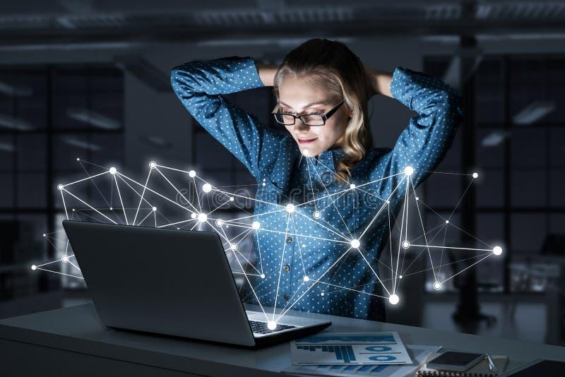 Aantrekkelijk blonde die glazen in donker bureau dragen die laptop met behulp van Gemengde media stock afbeelding
