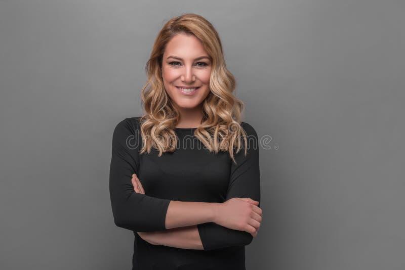 Aantrekkelijk blonde in donkere kleren op een grijze achtergrond royalty-vrije stock fotografie