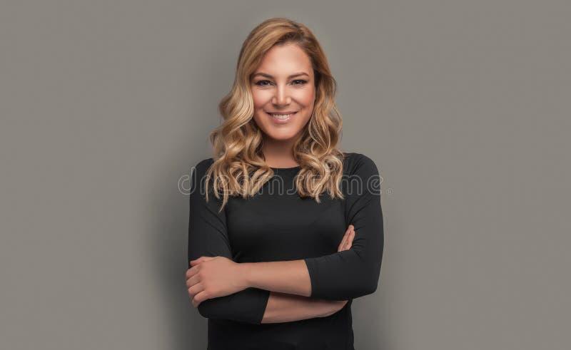 Aantrekkelijk blonde in donkere kleren op een grijze achtergrond royalty-vrije stock afbeeldingen