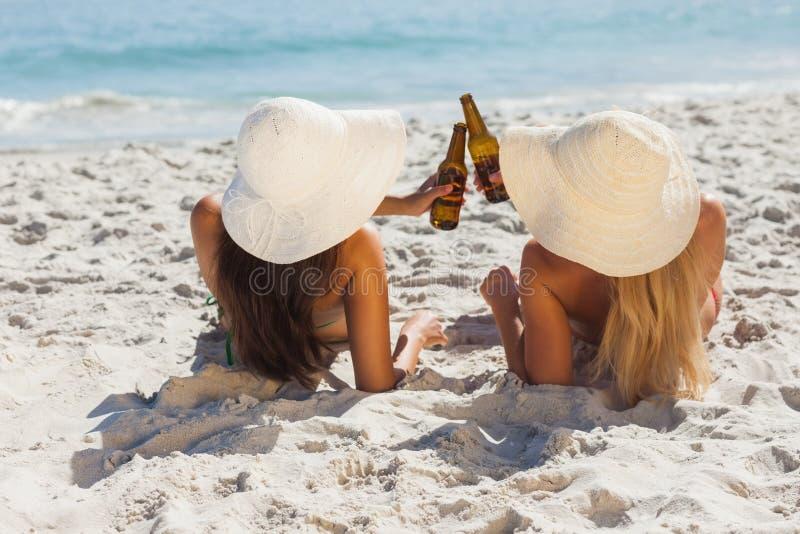 Aantrekkelijk blonde en brunette in bikinis die glasflessen clinking royalty-vrije stock afbeelding