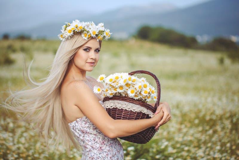 Aantrekkelijk blonde op kamillegebied. Jonge vrouw in kroon stock afbeeldingen