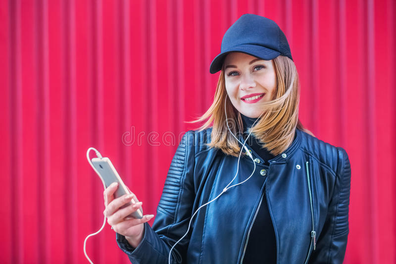 Aantrekkelijk blondemeisje die aan muziek op zijn smartphone luisteren stock foto's