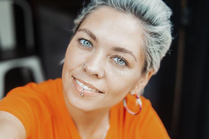Aantrekkelijk blondemeisje die in oranje T-shirt selfie bij koffie maken royalty-vrije stock fotografie