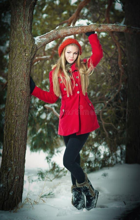 Aantrekkelijk blondemeisje met handschoenen, rode laag en het rode hoed stellen in de wintersneeuw. Mooie vrouw in het de winterla royalty-vrije stock foto