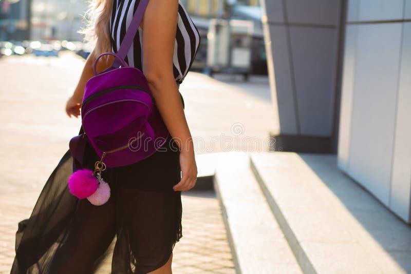 Aantrekkelijk blondemodel in kleding die bij de stad met een weinig purpere rugzak lopen Lege ruimte stock afbeeldingen