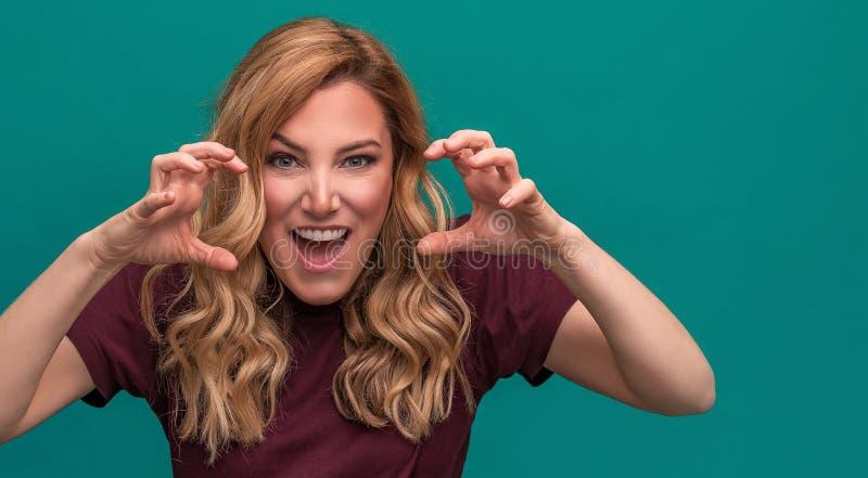 Aantrekkelijk boos blonde die voorbereidingen treffen aan te vallen of te krassen Boze jonge vrouw op blauwe achtergrond royalty-vrije stock foto
