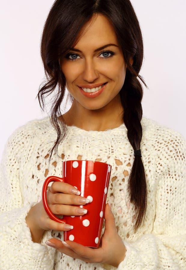 Aantrekkelijk brunette die een rode mok houden royalty-vrije stock afbeelding