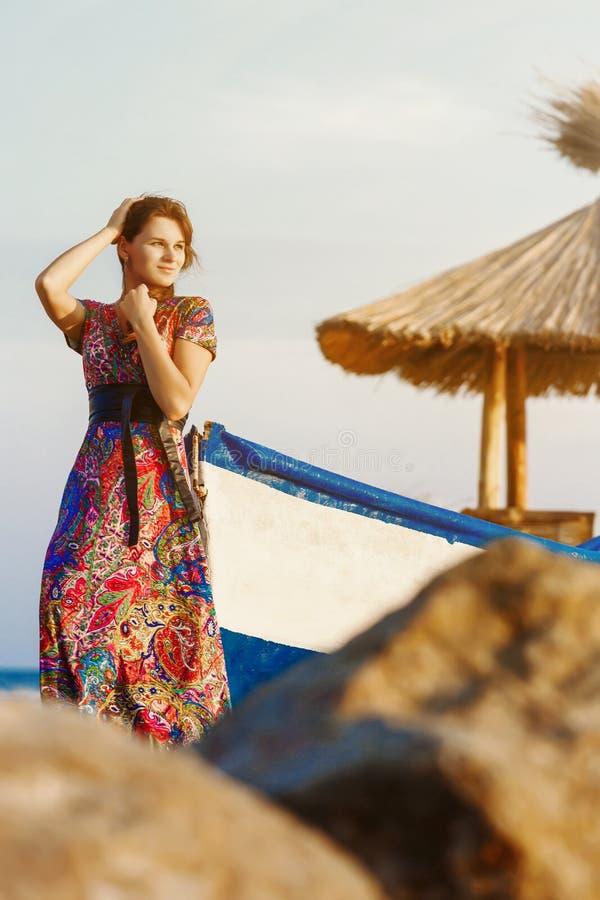 Aantrekkelijk brunette in lange kleurrijke kleding die zich alleen op het strand dichtbij de boot bij zonsondergang bevinden stock foto's
