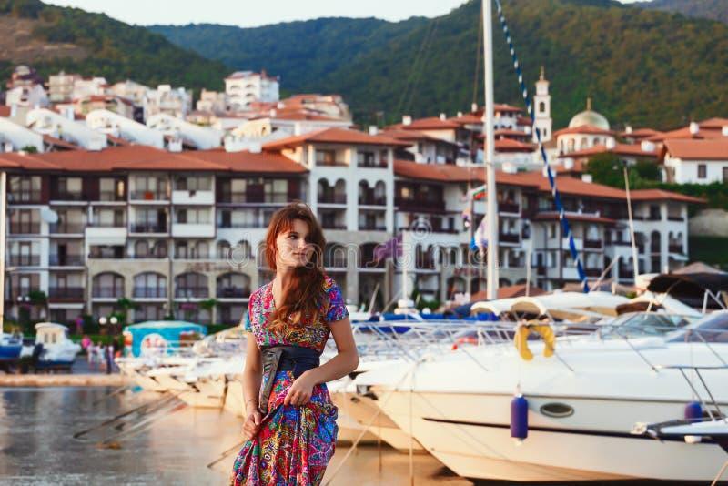 Aantrekkelijk brunette in lange kleurrijke kleding die zich alleen op het strand tegen de achtergrond van jachten en stad bij zon stock foto's
