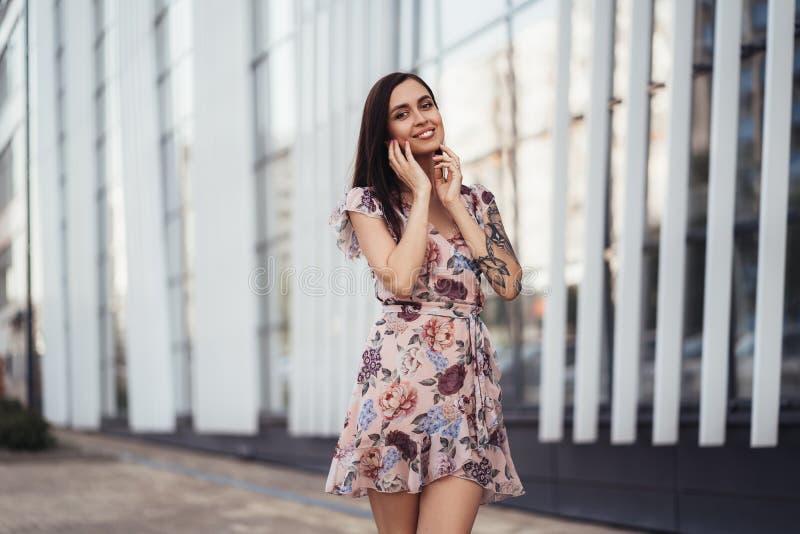 Aantrekkelijk donkerbruin meisje in het gekleurde kleding stellen dichtbij de moderne bouw royalty-vrije stock afbeeldingen