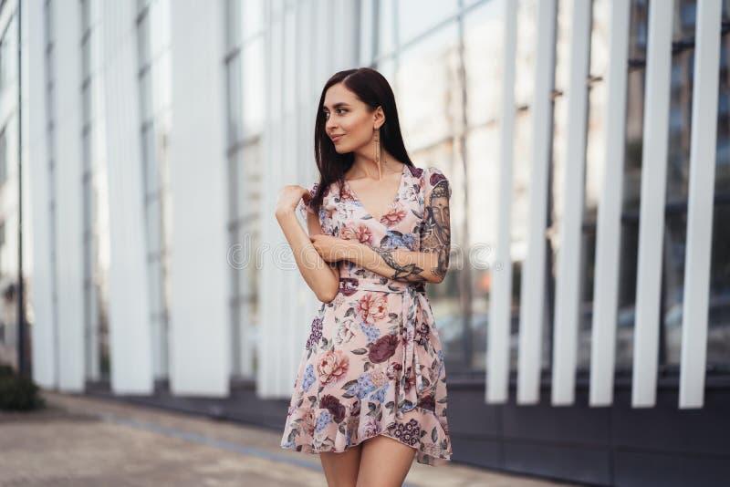 Aantrekkelijk donkerbruin meisje in het gekleurde kleding stellen dichtbij de moderne bouw royalty-vrije stock fotografie