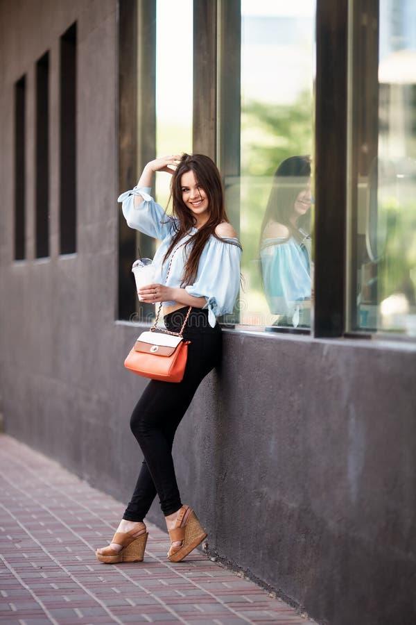 Aantrekkelijk donkerbruin meisje met lang haar die zich dichtbij koffie bevinden Zij draagt Blauwe blouse met open schouders stock fotografie
