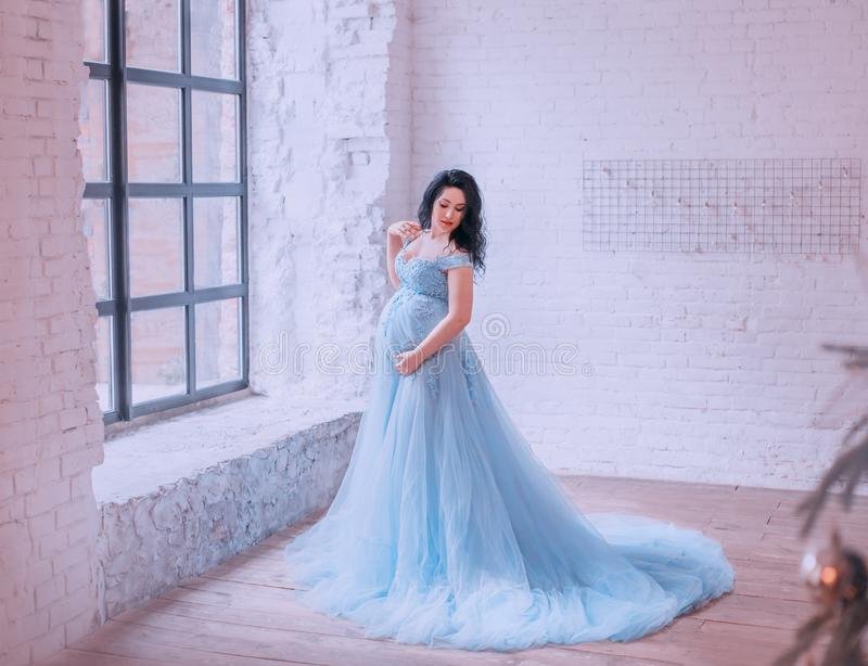 Aantrekkelijk donkerbruin zwanger meisje in ruime ruimte met witte bakstenen muur door venster, die in de foto, in lang blauw ste stock afbeeldingen