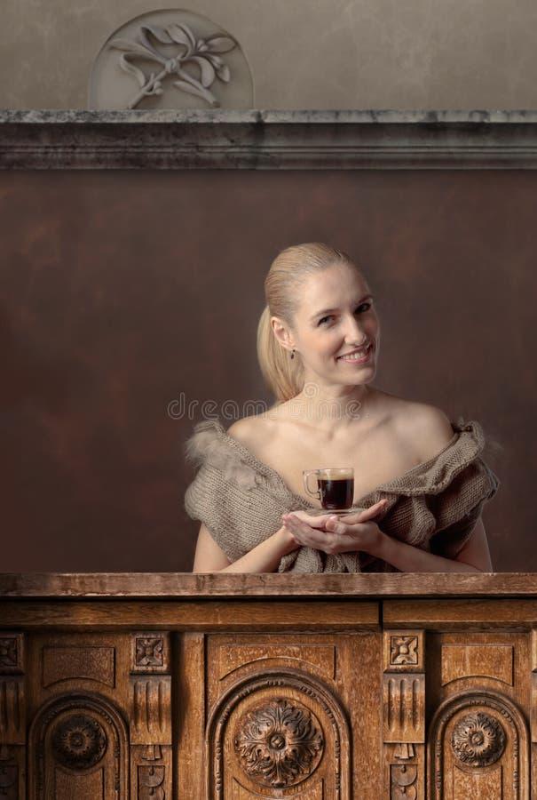 Aantrekkelijk en gelukkig blonde met een Kop van koffie bij de bar stock foto