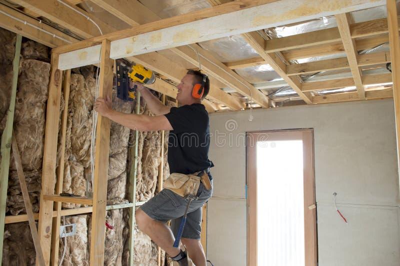 Aantrekkelijk en zeker van de aannemerstimmerman of bouwer mensen werkend hout met elektrische boor bij industriële bouwwerf stock afbeeldingen