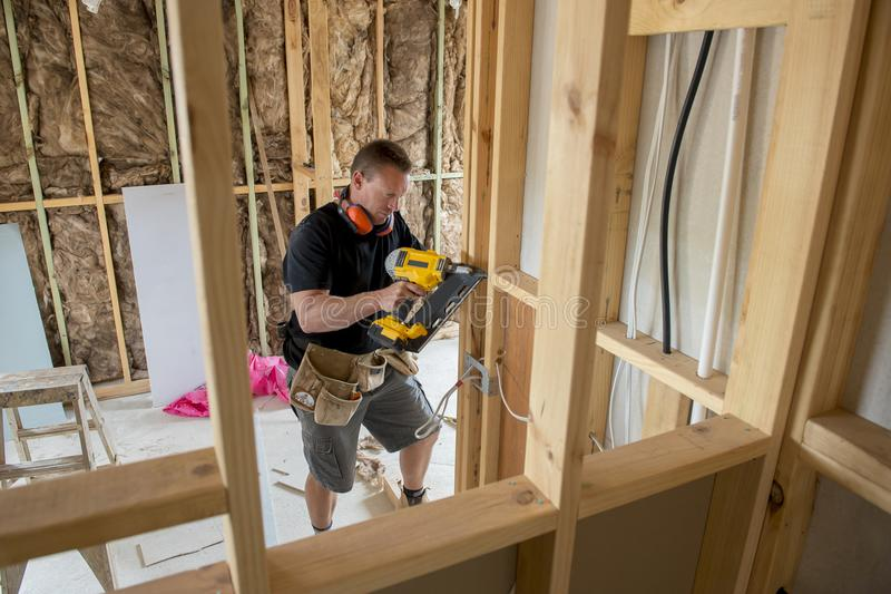 Aantrekkelijk en zeker van de aannemerstimmerman of bouwer mensen werkend hout met elektrische boor bij industriële bouwwerf royalty-vrije stock foto
