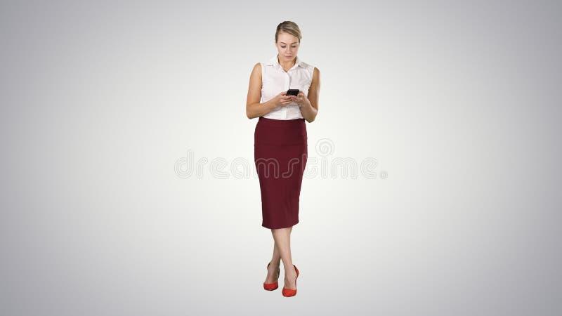 Aantrekkelijk Europees wijfje met smartphone in hand, wat betreft het scherm met vinger aan typebericht op gradiëntachtergrond royalty-vrije stock fotografie