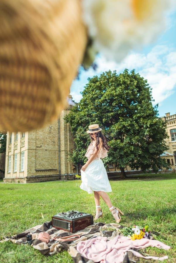 aantrekkelijk gelukkig donkerbruin meisje in uitstekende kleren die op gras stellen royalty-vrije stock afbeeldingen