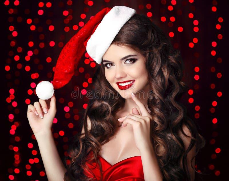 Aantrekkelijk gelukkig glimlachend meisje in santahoed met het rode lippen stellen stock afbeeldingen