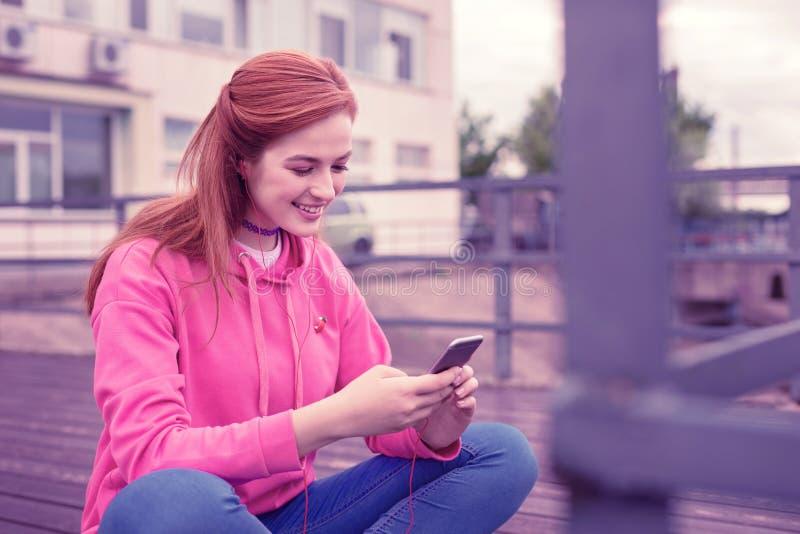 Aantrekkelijk gembermeisje in heldere hoodie die met informatie in sociale media worden tevredengesteld stock fotografie