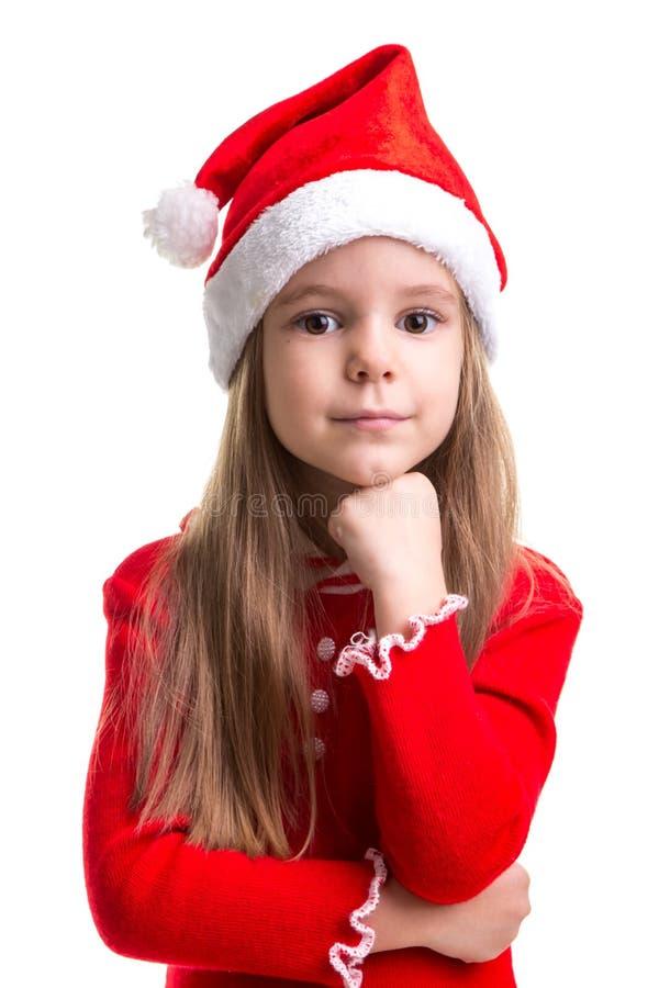 Aantrekkelijk glimlachend Kerstmismeisje met een vuist onder de kin, die een santahoed dragen over een witte achtergrond wordt ge stock foto